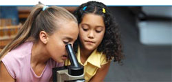 Elementary school girls at a microscope