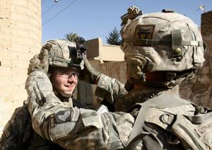 Soldier adjusting another's helmet